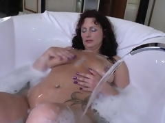 Older in a soapy bathtub masturbates solo
