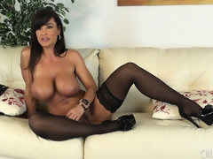 Lisa Ann poses seductively in a couple of stockings and high heels
